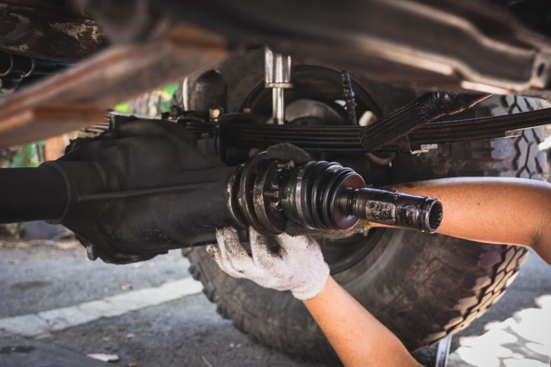 Hands fixing car axle.