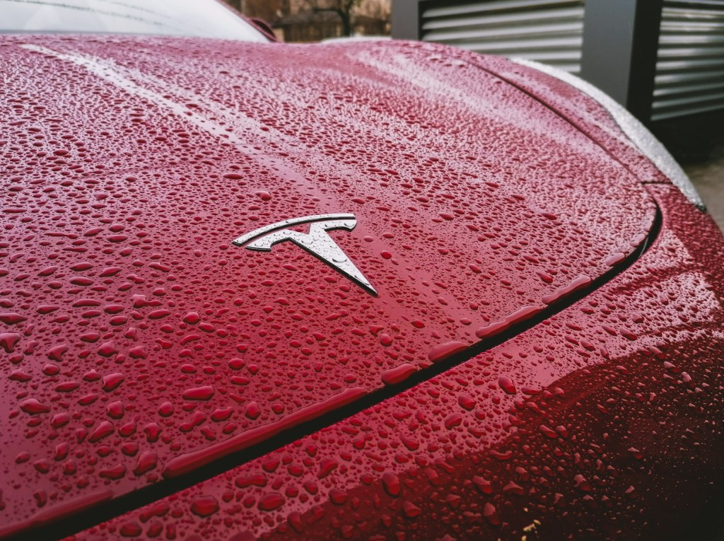 Close up of red Tesla in the rain with logo.