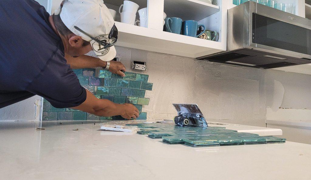 Man installing tile backsplash.