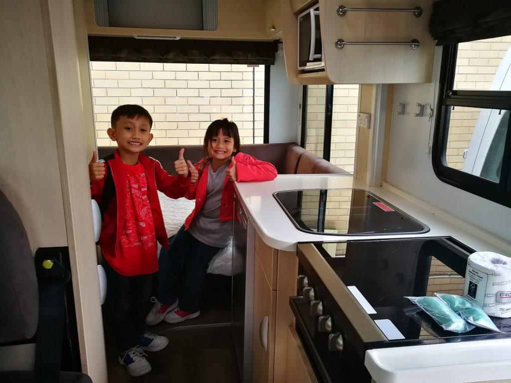 Two children happy in RV kitchen