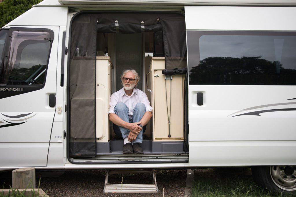 Old man sitting in van.