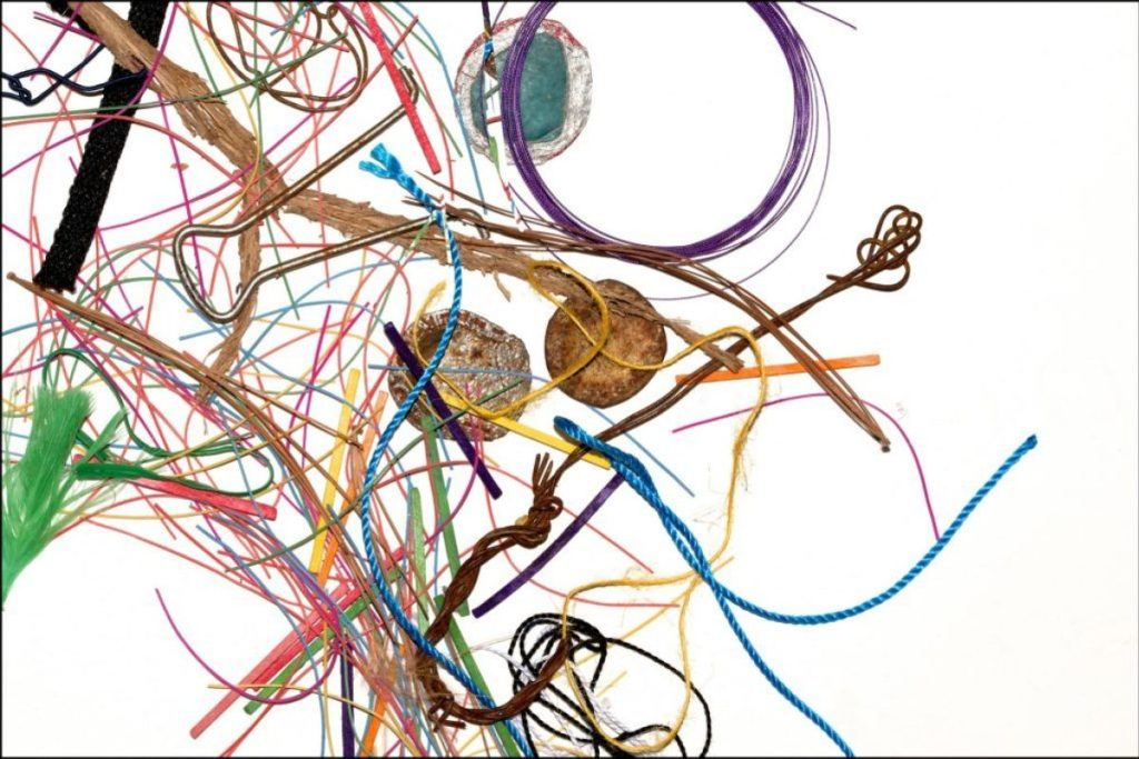 Abstract photograph with paint, string, bottle caps, sticks