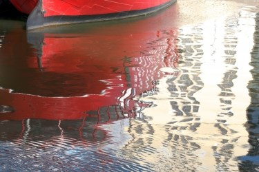 Photograph of bottom of red boat reflected in illuminated water with ripples, taken for healing by a medical doctor