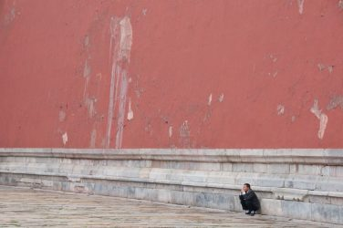 Photograph of person squatting against marble base of red wall, taken for healing by a medical doctor