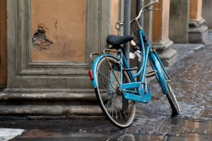 Photograph of blue bike leaning against tan wall