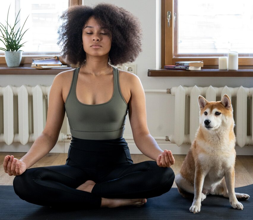 girl sitting next to dog meditating
