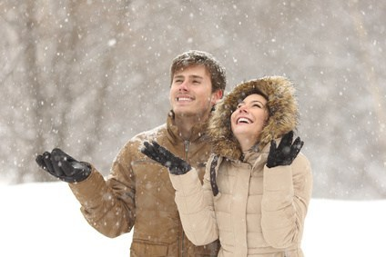 Couple together smiling and looking at the snow falling from the sky to represent Dr. Karen Gless post Staying Sane during the Season