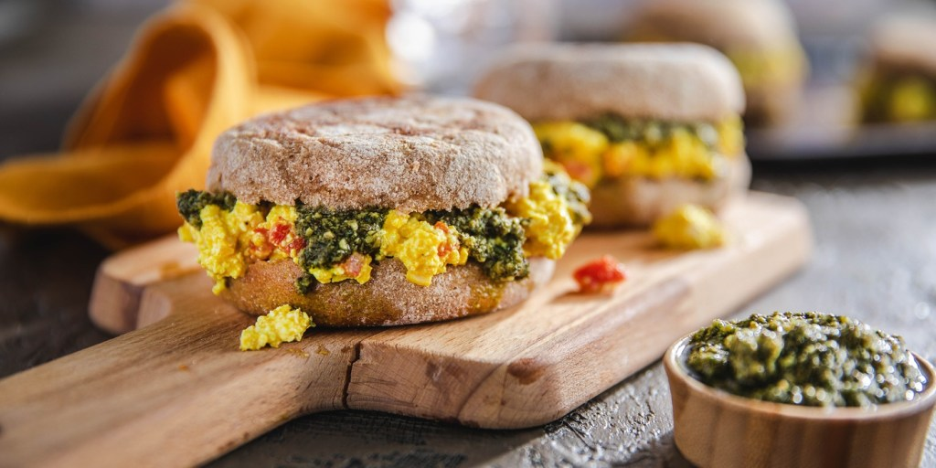 vegan egg sandwiches with spinach and peppers on a wooden board