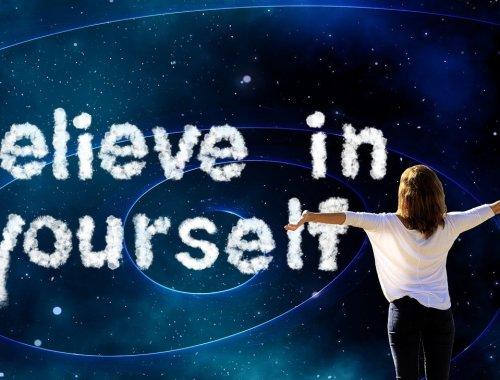 kobieta z otwartymi ramionami na ciemnym tle i napis believe in yourself