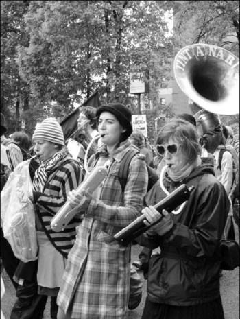 Trois filles de la fanfare Tintanar, jouant des instruments à vent, vêtues de manière originale.