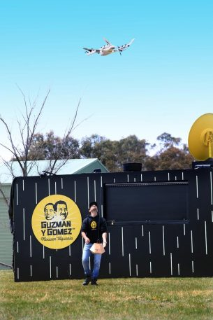 A Guzman y Gomez employee walks outside the kitchen to load a package containing a burrito onto a hook that is winched up by the Wing delivery drone
