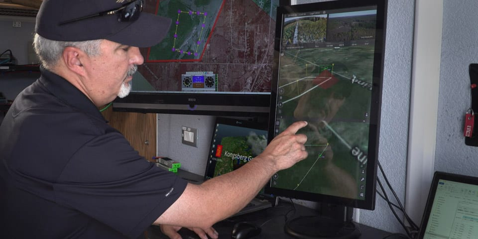IRIS UAS program director Paige Cutland uses the IRIS UAS airspace situational awareness application to monitor the progress of a drone on a beyond line-of-sight (BVLOS) mission from a portable ground control station set up in a trailer.