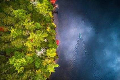 Aerial view of a kayaker enjoying the Autumn Colors in a lake in New Hampshire. My drone helps me to see the world with a unique perspective.