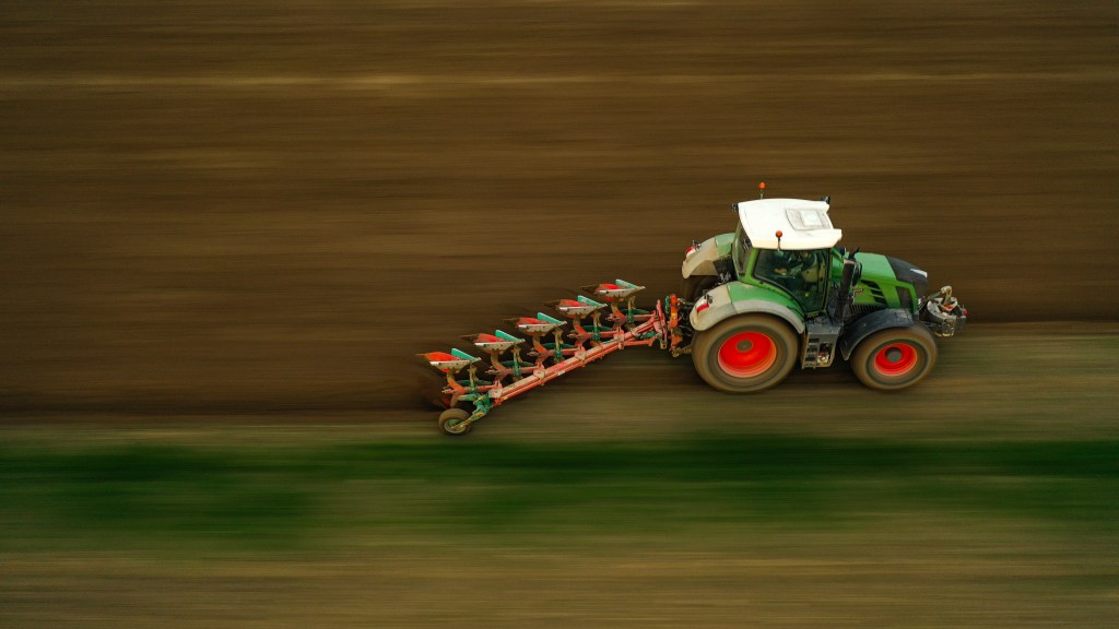 This image from from a blog post on the Drone Photography Bible. The article is How To Take Perfect Panning Photos From A Drone? The photo is a panning shot of a tractor taken from a drone. The tractor is sharp but the background is blurred due to long exposure.