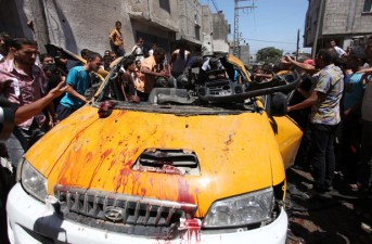 Palestinians gather around a taxi in which four members of the Abu Daqqa family were killed in a reported Israeli drone strike on Khan Younis, southern Gaza Strip, on 16 July.  (Ramadan El-Agha / APA images)