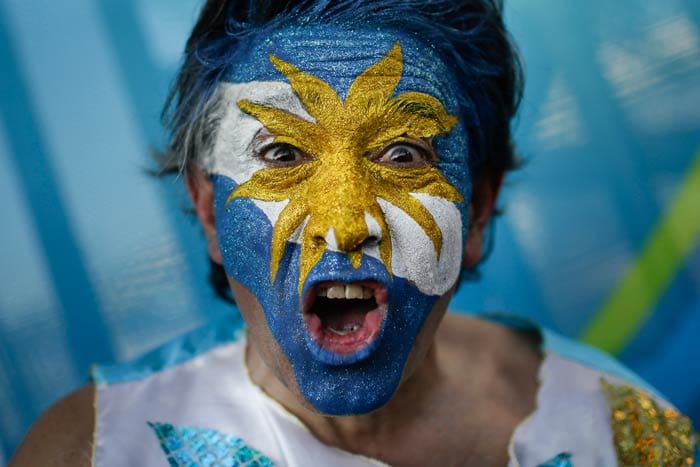 A fan cheers for Argentina with his face painted to represent his country's national flag.