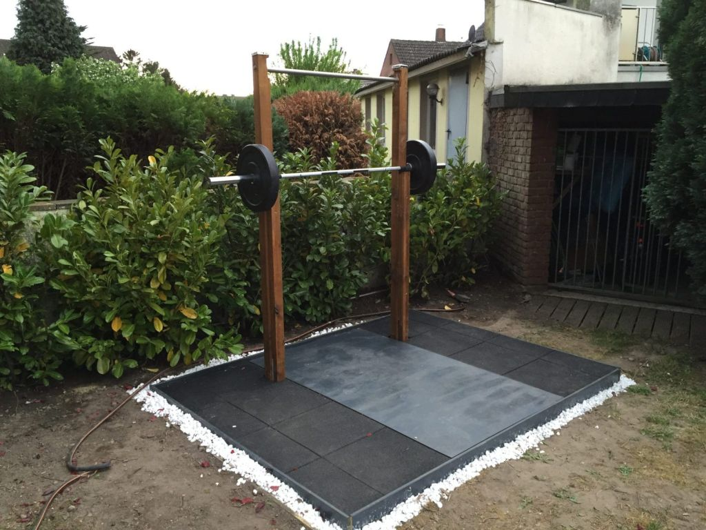 A professional-looking lifting platform with Olympic barbell and rack.