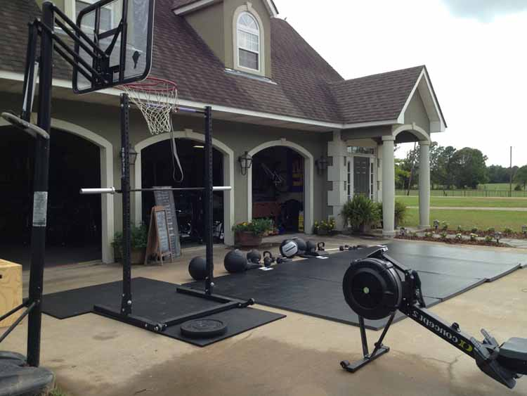 A half rack and Olympic barbell with medicine balls, kettlebells, rowing machines and other sporting equipment at a grand-looking dwelling.