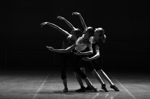 Three dancers extend their legs in sync with each other.