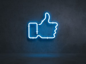 A blue neon sign in the shape of a thumbs-up