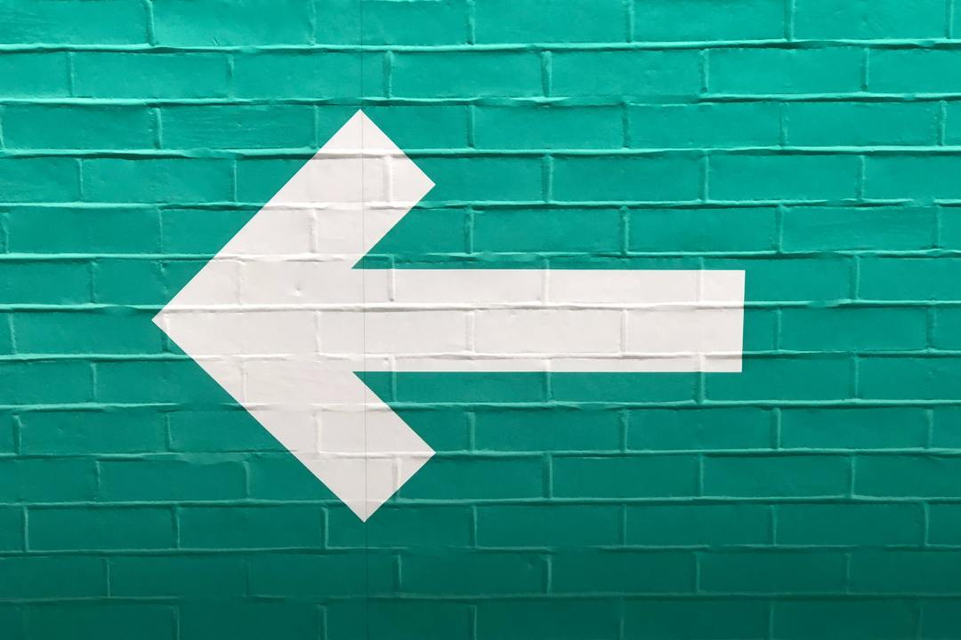 A bold white arrow pointing left is painted onto a bright teal brick wall.