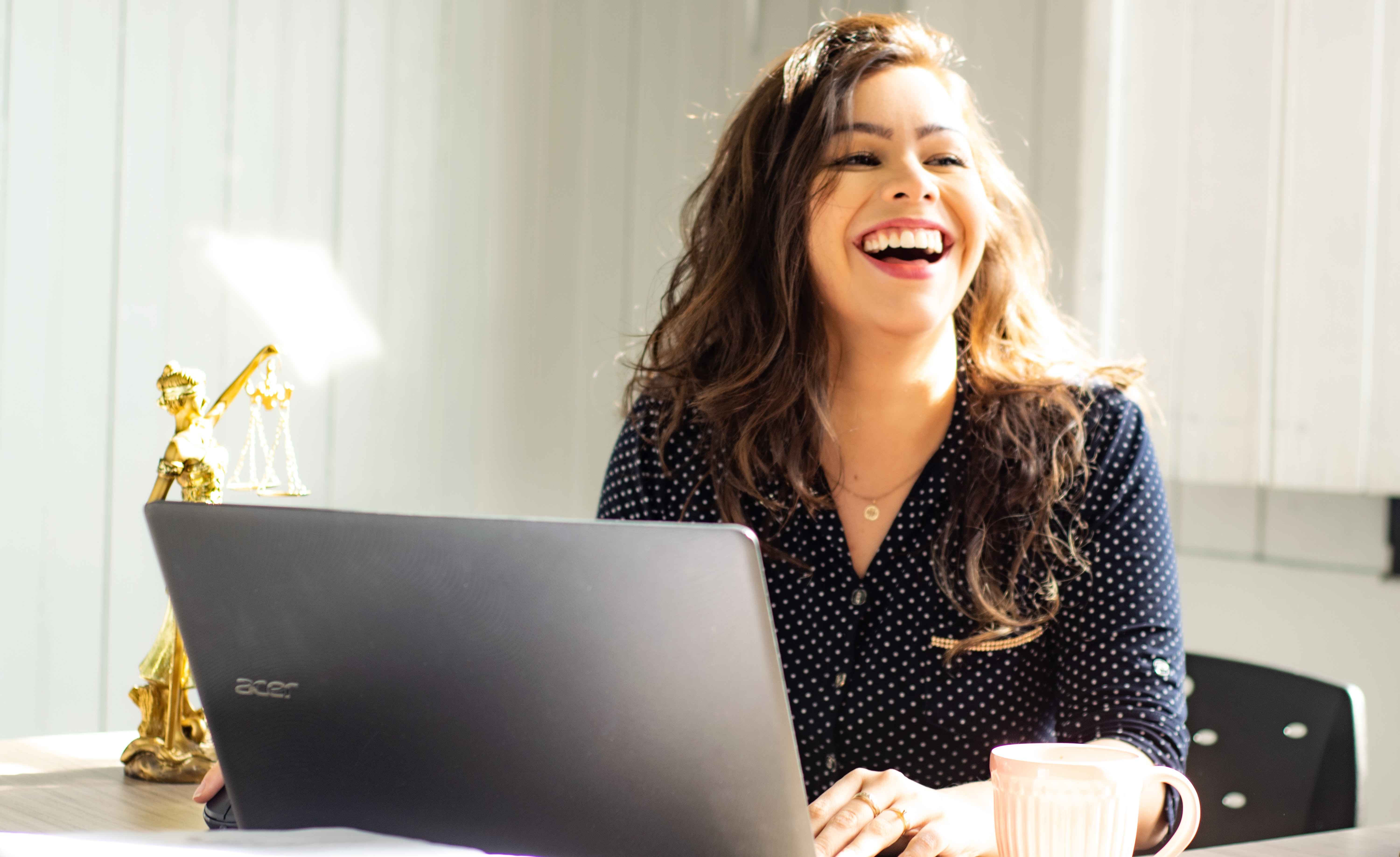 A woman laughs while sitting at an elegant desk with a laptop open on it.
