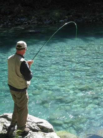 Catching Trout in Crystal Waters of New Zealand