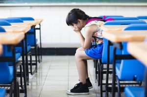 AdobeStock 88718689 - sad girl sitting and  thinking in the classroom