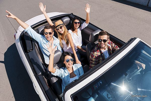 Traveling with fun. Top view of young happy people enjoying road trip in their white convertible and raising their arms