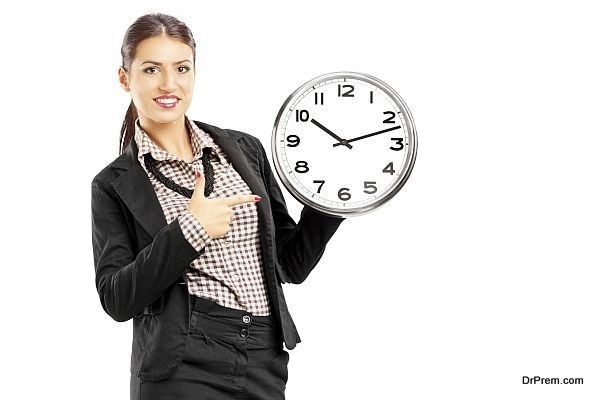 Smiling female standing and pointing on a wall clock, isolated on white background