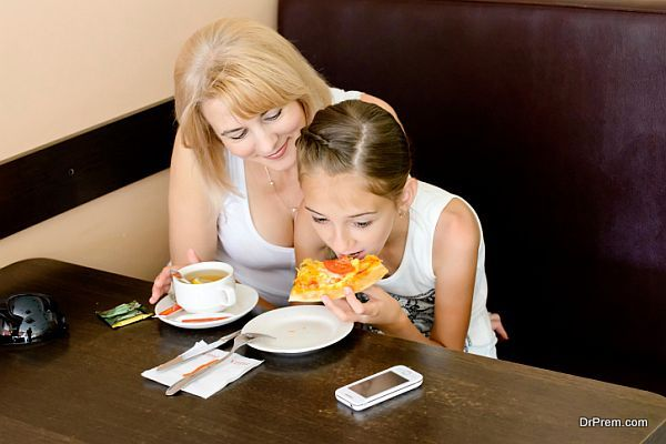 Mother and daughter eating pizza