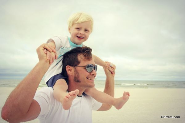 A young father has his toddler son on riding on his shoulders, and they are playing on the white sand beach by the ocean on a family summer vacation.
