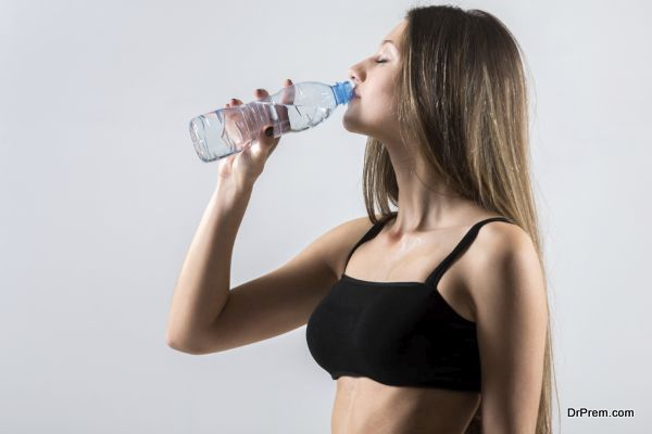 Slender sporty girl drinking water, resting after fitness exercises, tired, copy space