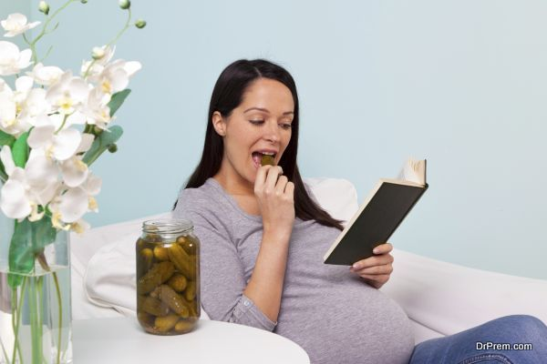 Photo of a pregnant woman at home sitting in an armchair with a craving for pickled gherkins.
