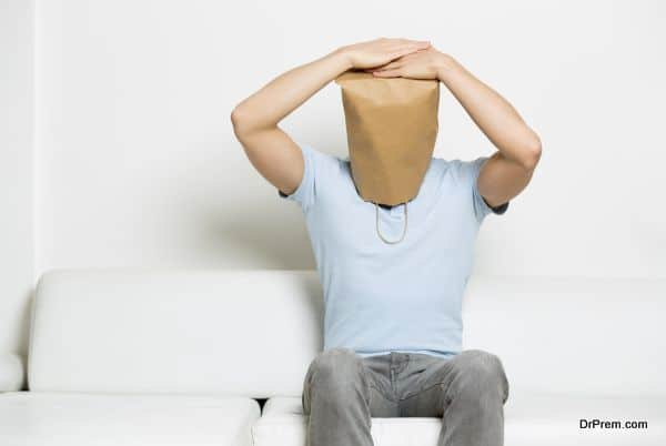 Miserable anonymous man with head covered sitting on sofa.