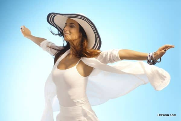 Attractive young woman pretending to fly, enjoying sun and wind eyes closed.