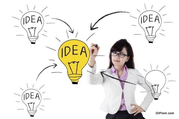 Business woman drawing light bulb with her black marker