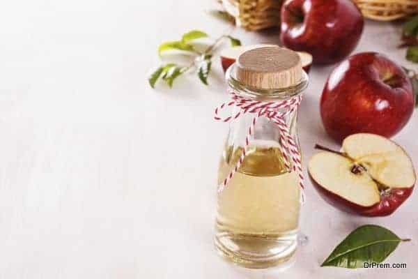 Apple cider vinegar and red apples over white wooden background with copyspace. Selective focus