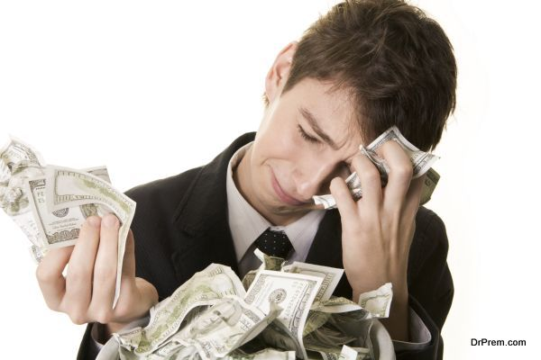 Conceptual image of grieving young businessman over heap of crumpled dollars