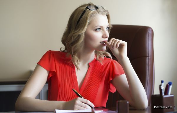 Attractive young elegant smart blonde working business woman sitting in office on brown leather chair in red blouse and glasses thinking and writing looking away indoor on white background, horizontal picture