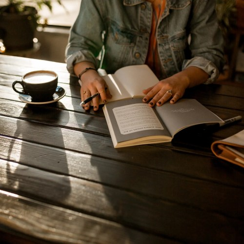 Image of a woman with coffee and journal to represent the reflection that goes along with coaching