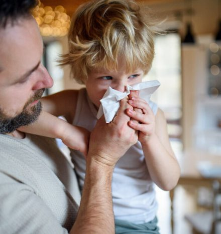 Mature father blowing nose of small sick son indoors at home.