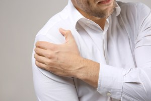 man in white shirt experiencing shoulder pain