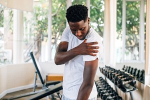man standing and suffering from shoulder pain during workout with dumbbells