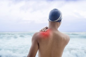 man with shoulder pain before swimming