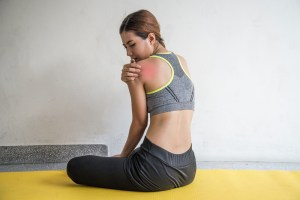 Woman with shoulder pain on yellow yoga mat