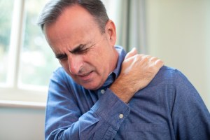 mature man suffering from frozen shoulder at home