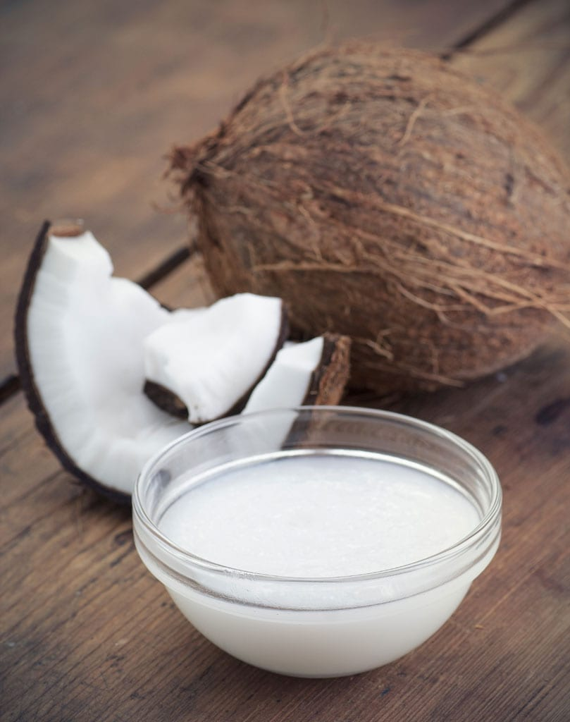 Coconuts and organic coconut oil in a glass jar