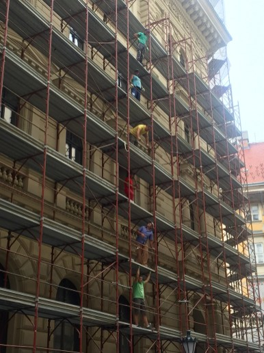 Construction workers passing beams and bricks down, organised by shirt colour.