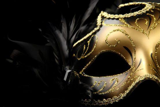 ornate carnival mask over black silk background